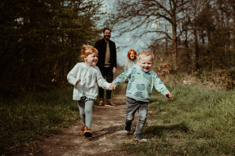 Kids running holding hands on family photoshoot in hertfordshire