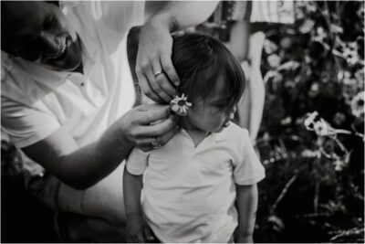 Dad putting flowers in sons hair on photoshoot