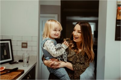 Mum and daughter laughing on natural family photoshoot